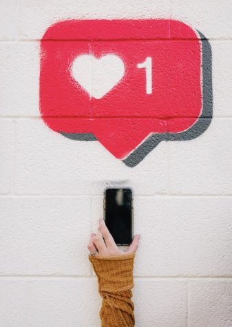 Hand holding phone with a spray painted image of a like heart from social media