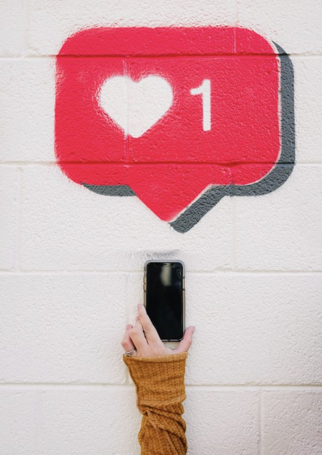 Hand+holding+phone+with+a+spray+painted+image+of+a+like+heart+from+social+media